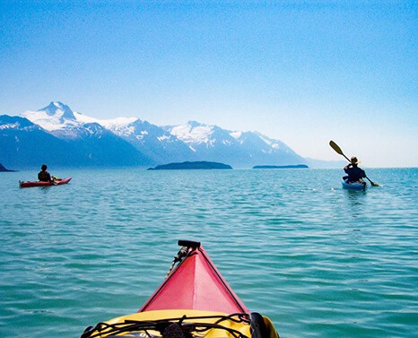 A sunny day Kayaking in Alaska with a snowy mountain view